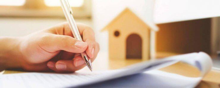Muž podepisující formuláře k dani z příjmu z prodeje nemovitosti
