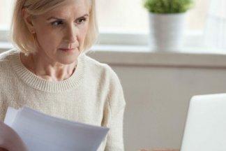 Starší žena si na internetu ověřuje své věřitele v insolvenčním rejstříku