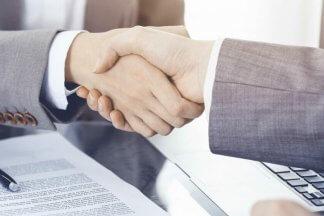 žena a muž si podávají ruce po podpisu smlouvy
