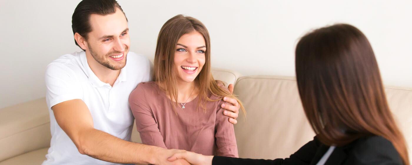Usmívající se pár radící se o tom, jak bezpečně pronajmout byt