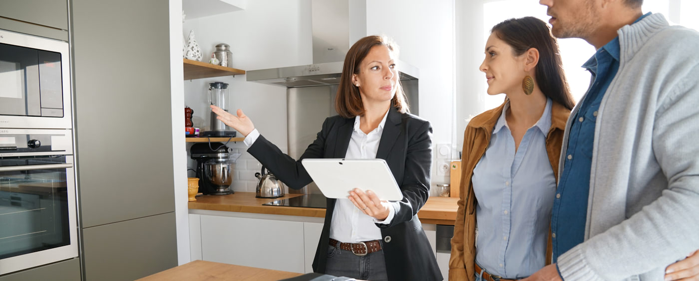 realitní makléřka ukazuje zájemcům o koupi kuchyň