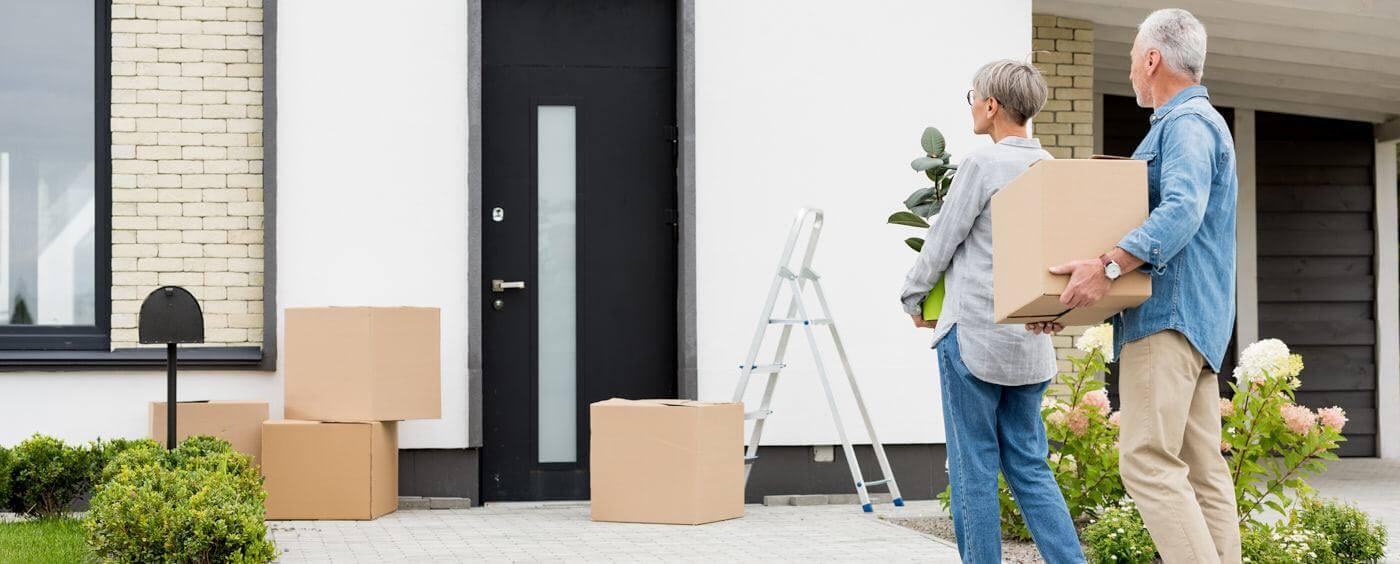 Starší pár nesou krabice s věcmi do svého nového domu