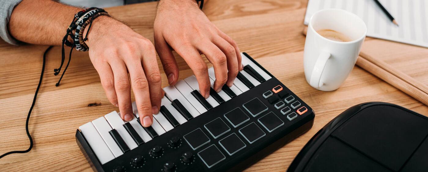 Ruce muže hrající na elektrickém pianu a vytvářející nahrávku, která je předmětem smlouvy o dílo.