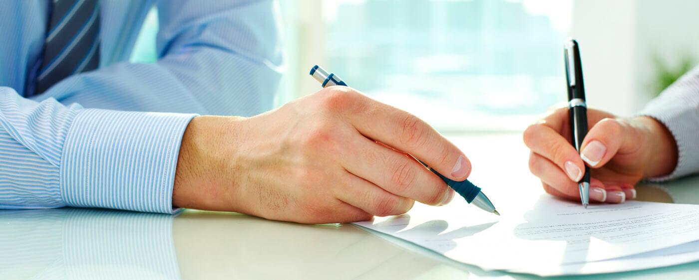 Pár rukou sepisující důležité náležitosti smlouvy o dílo