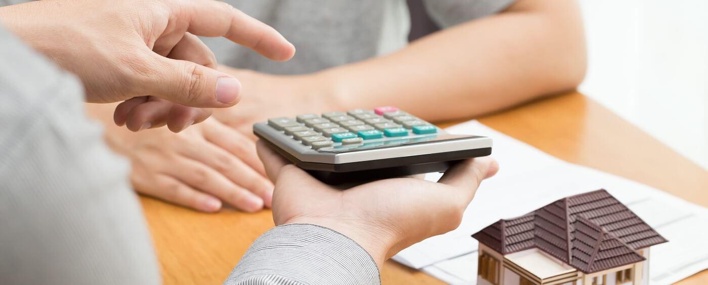 muž držící kalkulačku ukazuje druhé osobě jak počítat