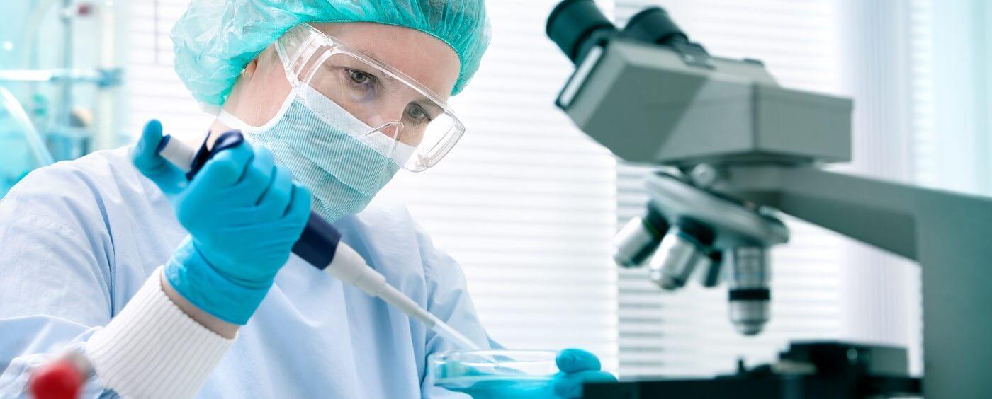 Vědkyně u mikroskopu s pipetou