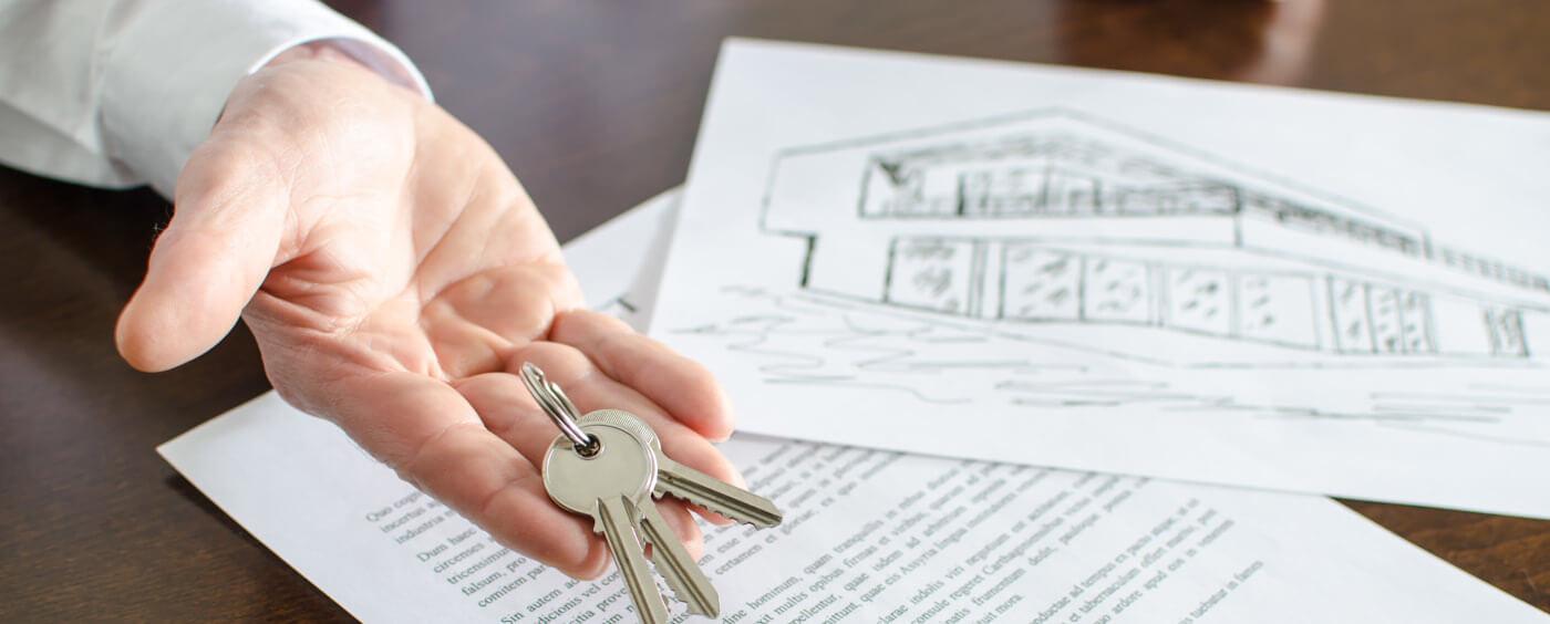 detail na ruce podepisující smlouvu a držící klíče