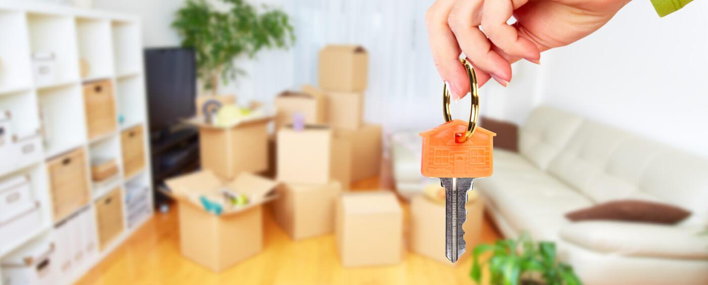 sbalené stěhovací krabice a v popředí ruka držící klíče