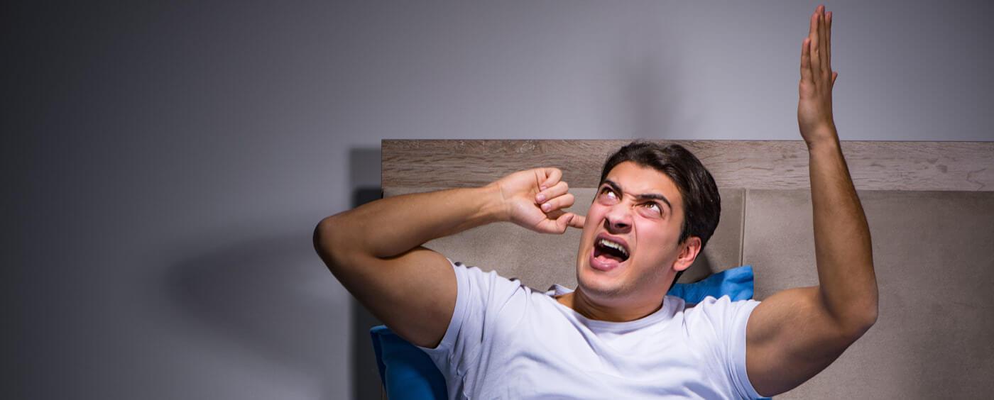 muž v posteli se rozčiluje nad hlučnými sousedy