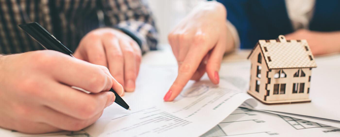 detail na ruce podepisující smlouvu, v popředí maketa domu
