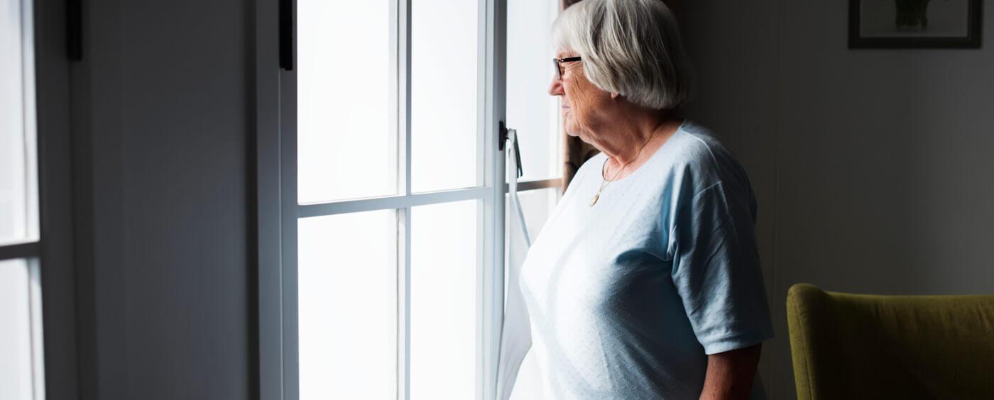 starší paní hledící z okna