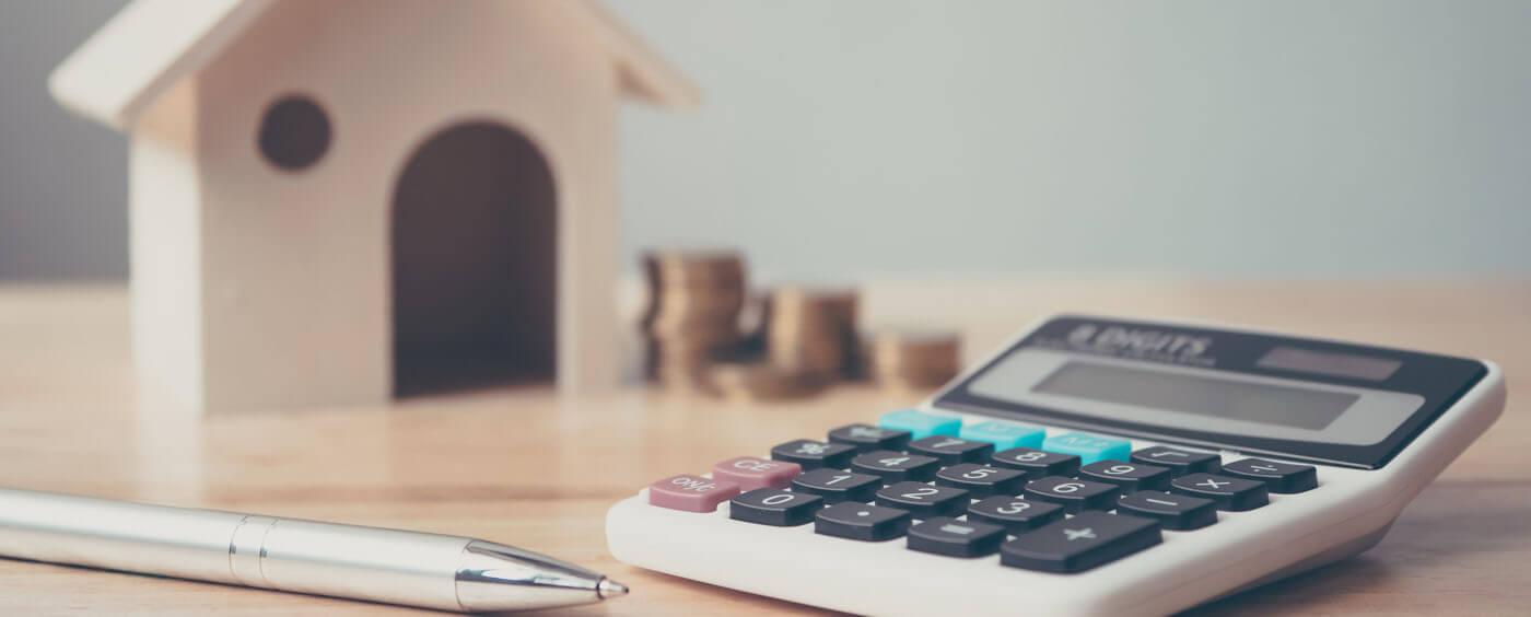 maketa domu v popředí s kalkulačkou a dokumenty