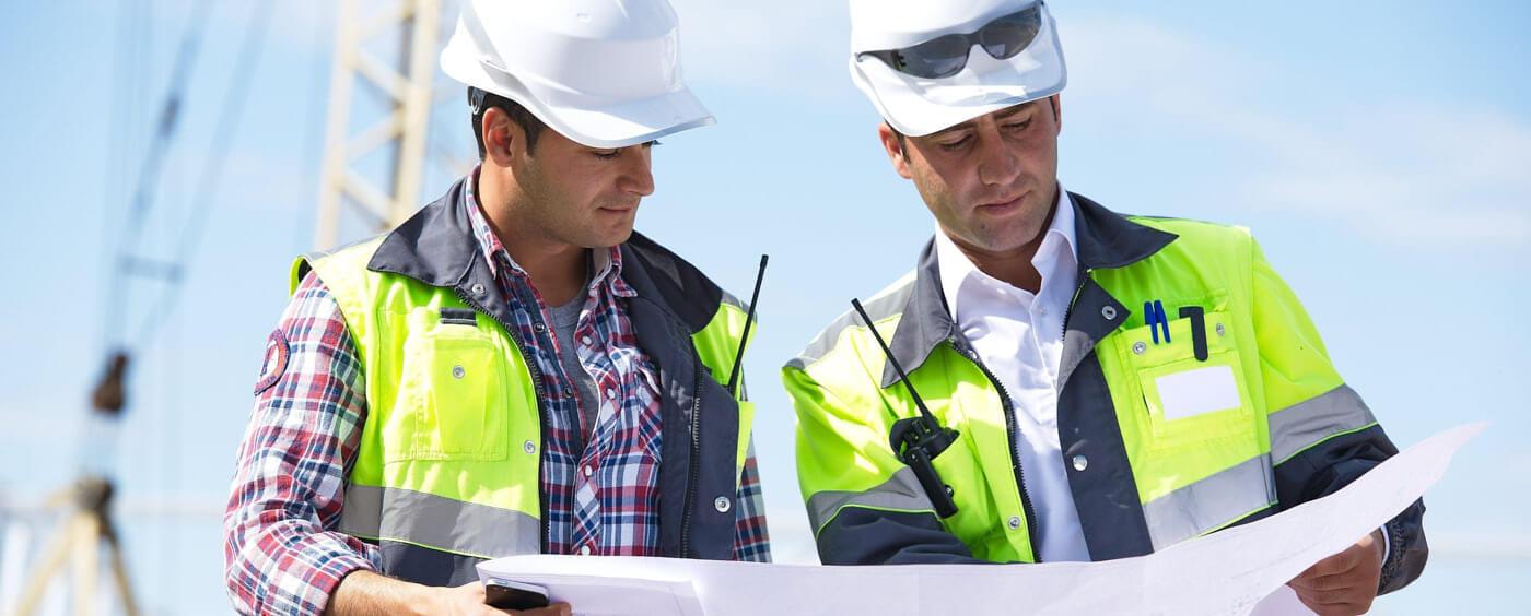 dva architekti na stavbě procházejí plány