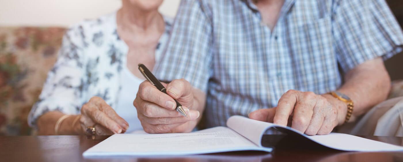 starší pár podepisuje dokumenty