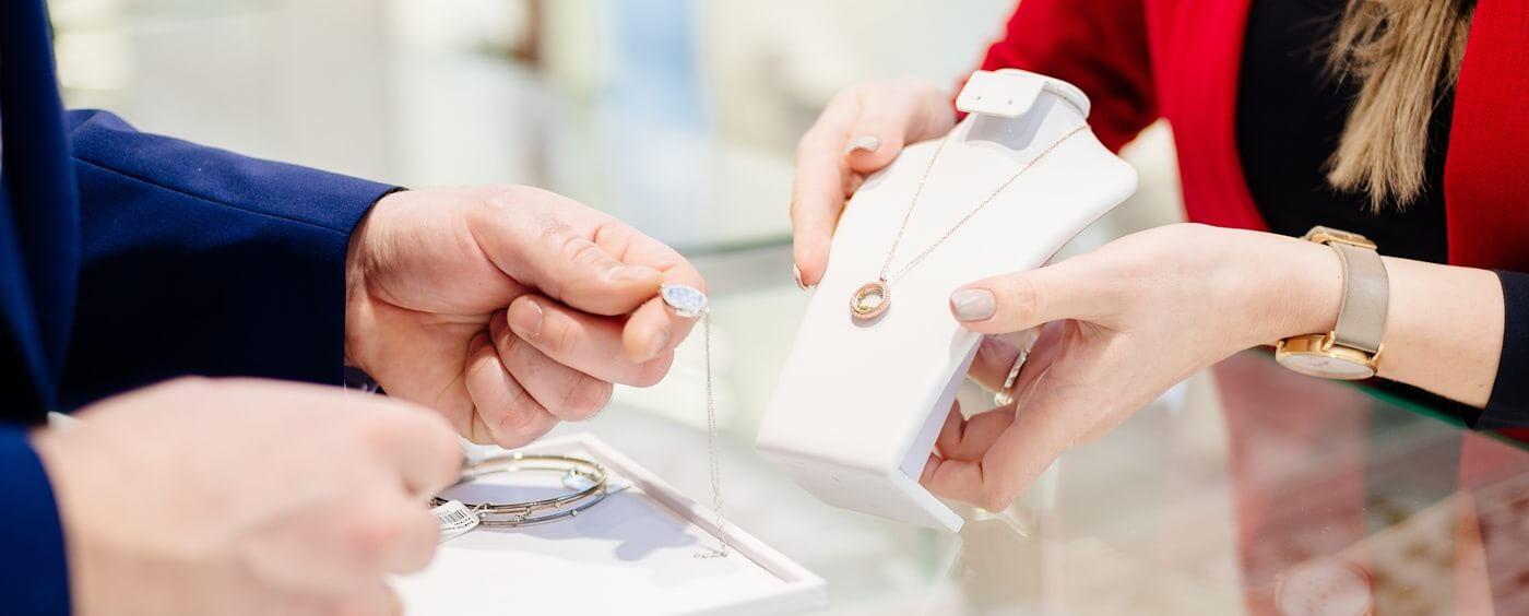 Prodavačka ukazuje zákazníkovi šperky nad prodejním pultem