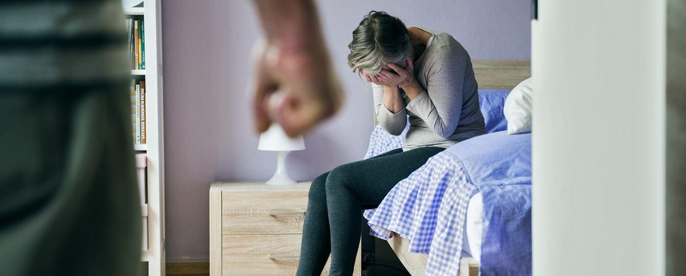 Žena sedící na posteli se obává fyzického napadení