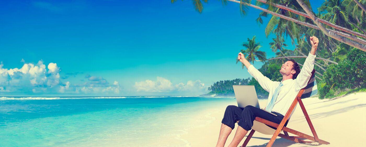 Muž s počítačem sedí na pláži na lehátku