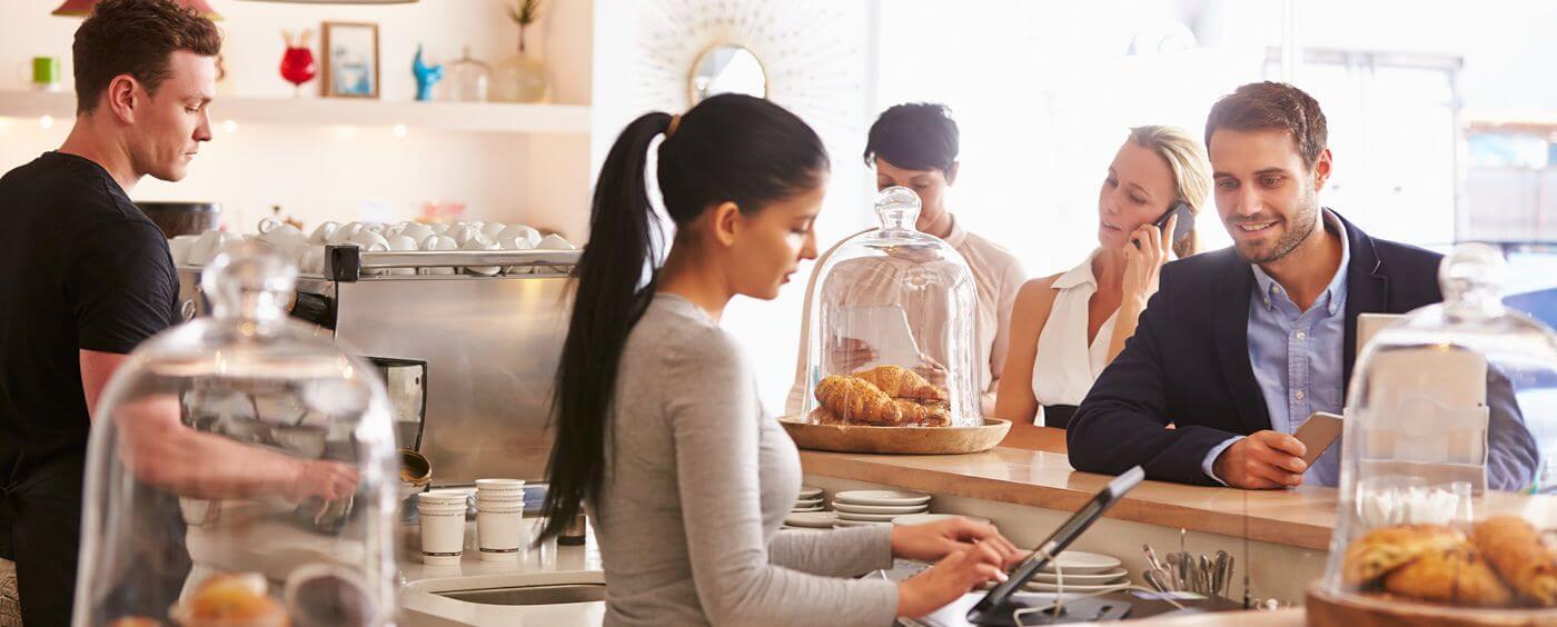 Servírka markuje zboží zákazníkovi za pultem