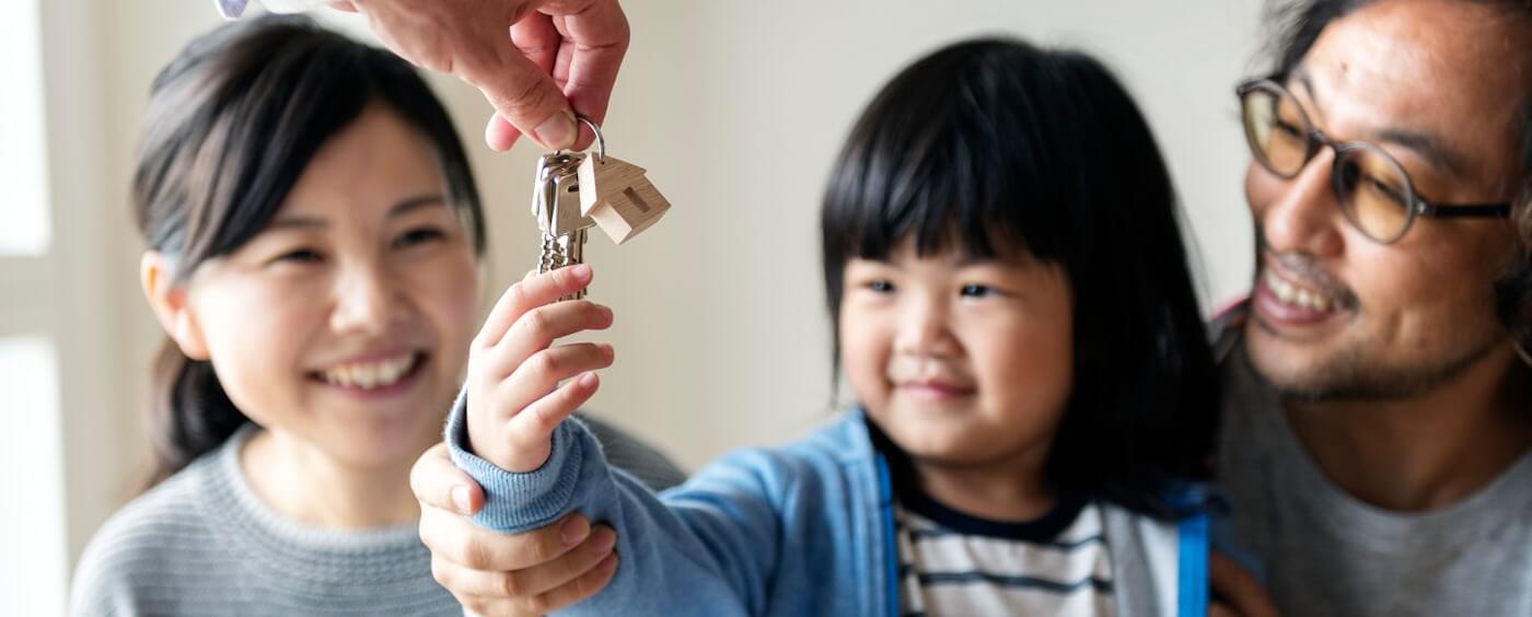 Dítě držící klíče, v pozadí její rodiče