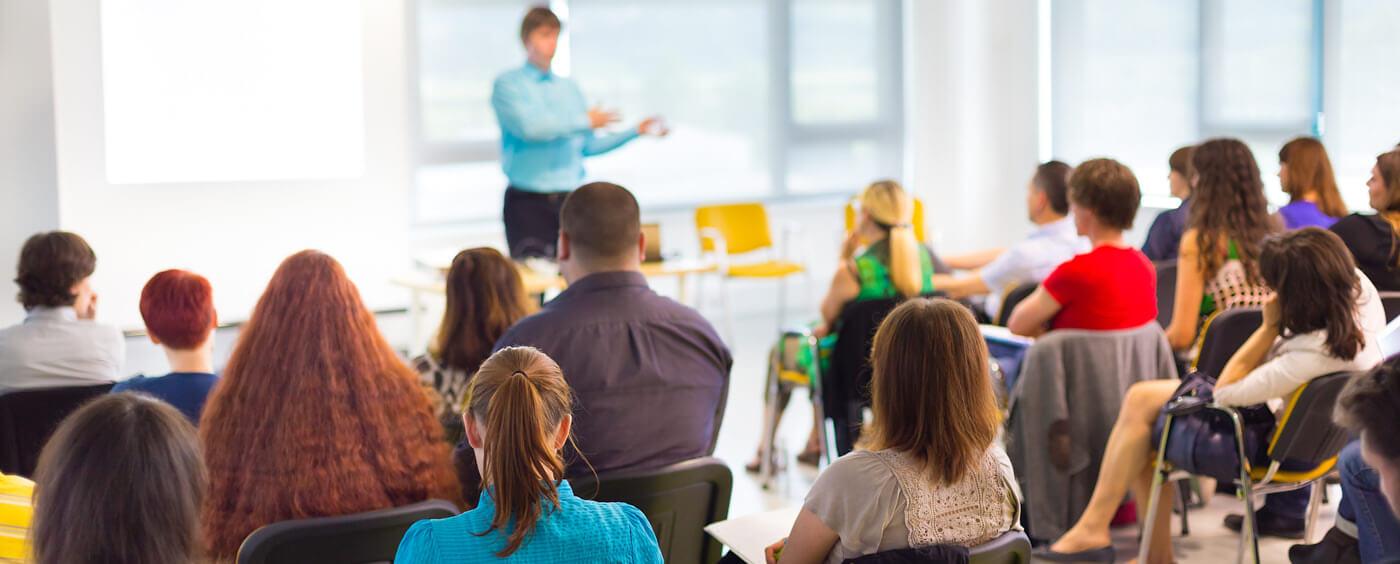 Skupina lidí na školení poslouchá přednášejícího