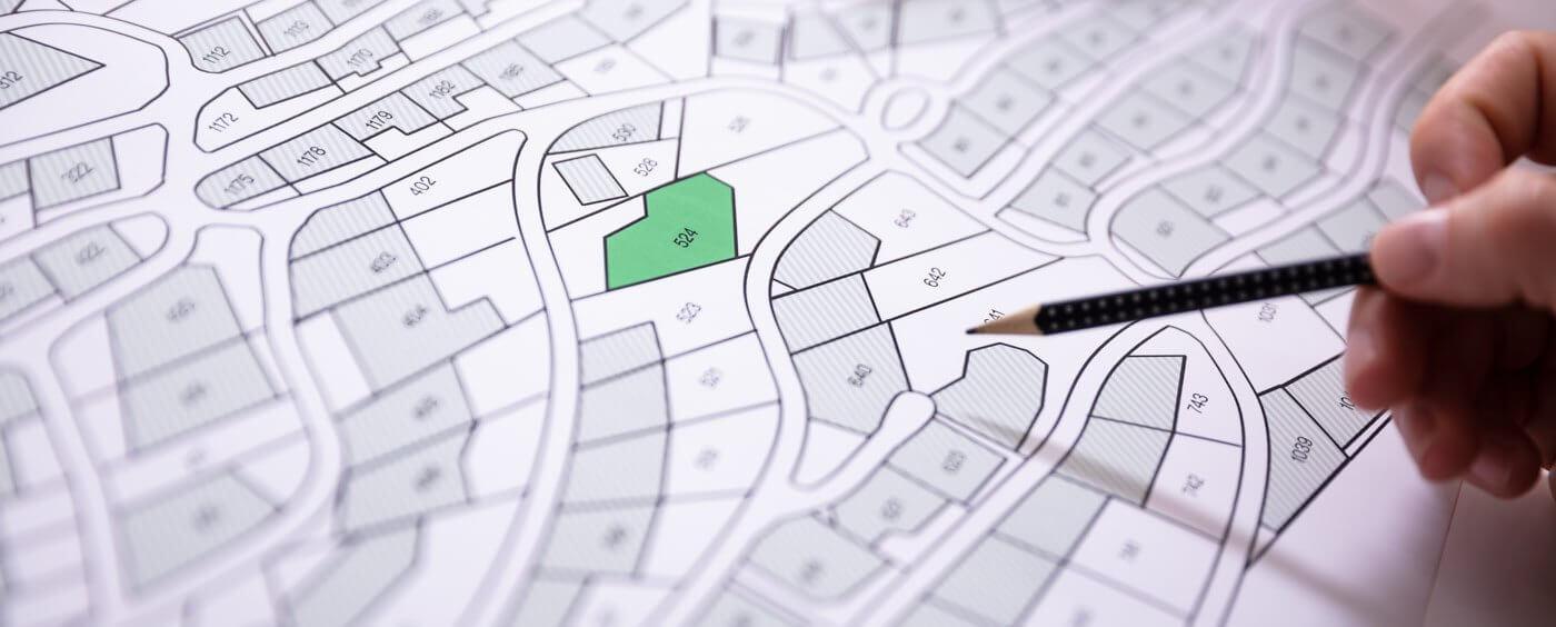 ruka s perem v ruce ukazuje na katastrální mapu