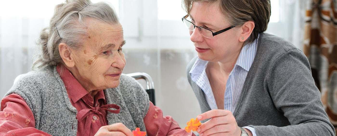 Starší paní a důchodkyně si povídají u stolu