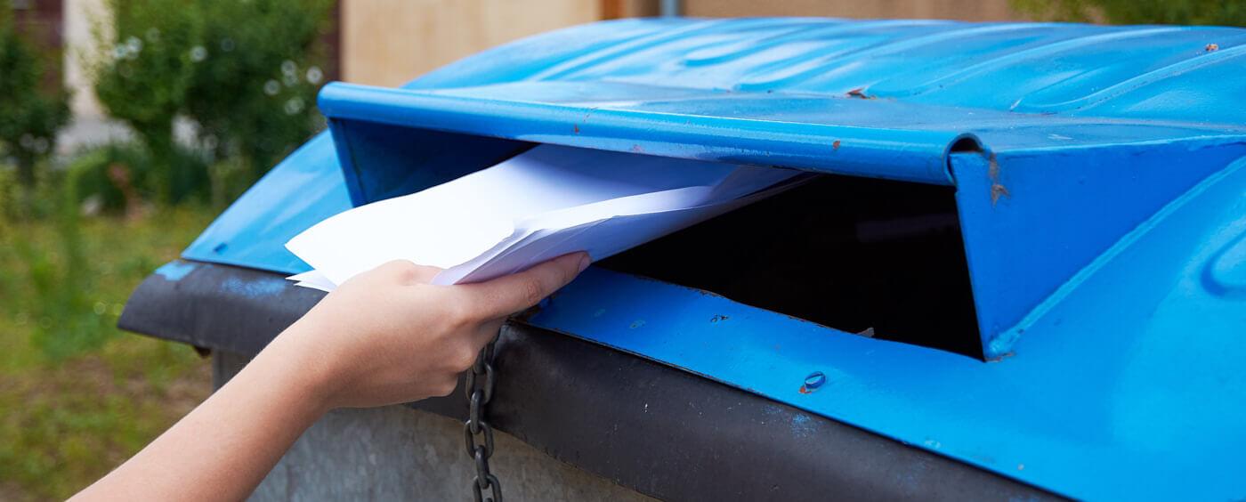 ruce házející dokumenty do popelnice