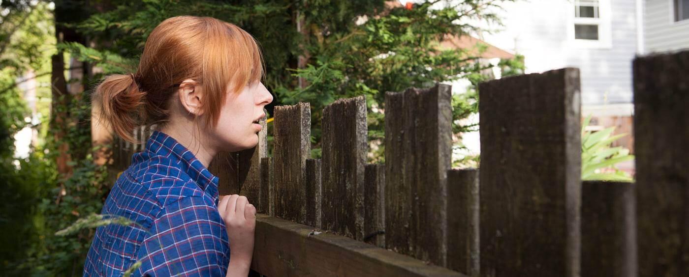 Žena stojící u vysokého plotu se dívá na sousedovu zahradu