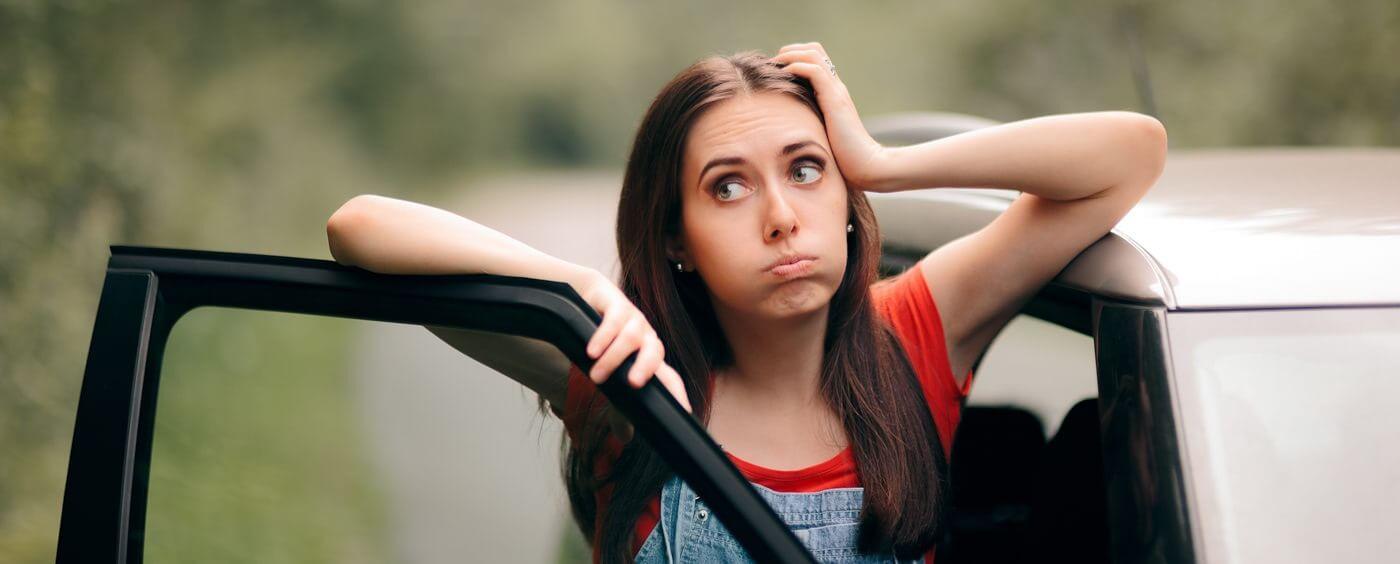 Žena stojící u auta si neví rady