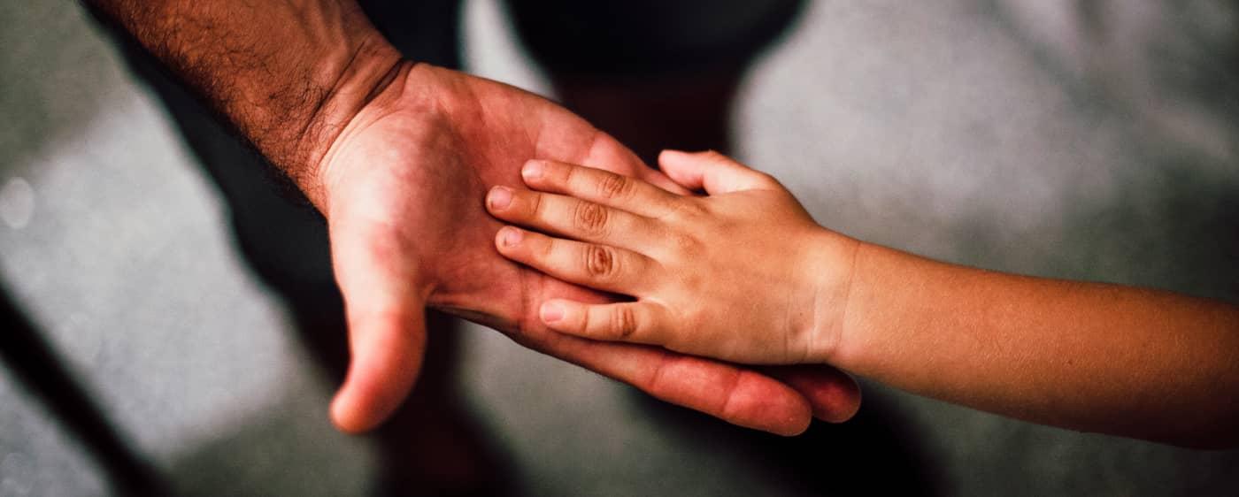 Ruce malého dítěte a otce řešícího náhradní výživné