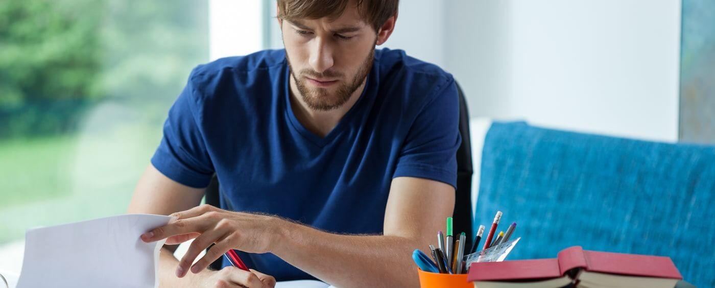 Muž studuje dokumenty a píše si poznámky