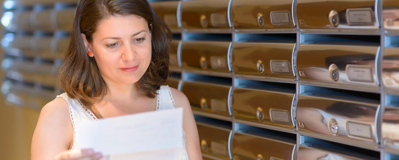 Žena v hale domu čte příchozí dopis
