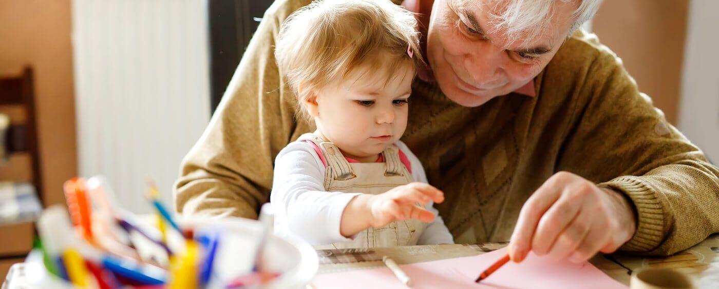 Děda se svoji vnučkou si kreslí u stolu