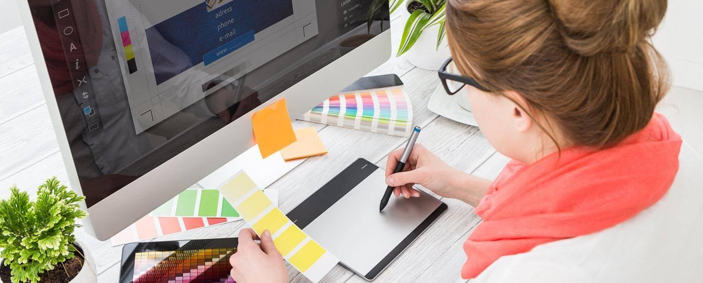 Žena sedící před počítačem zkouší barevné kombinace se vzorníkem