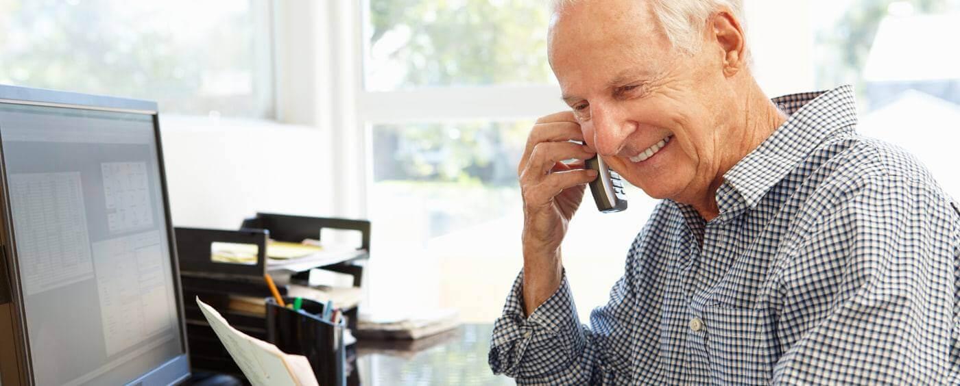 Starší muž telefonuje u svého pracovního stolu
