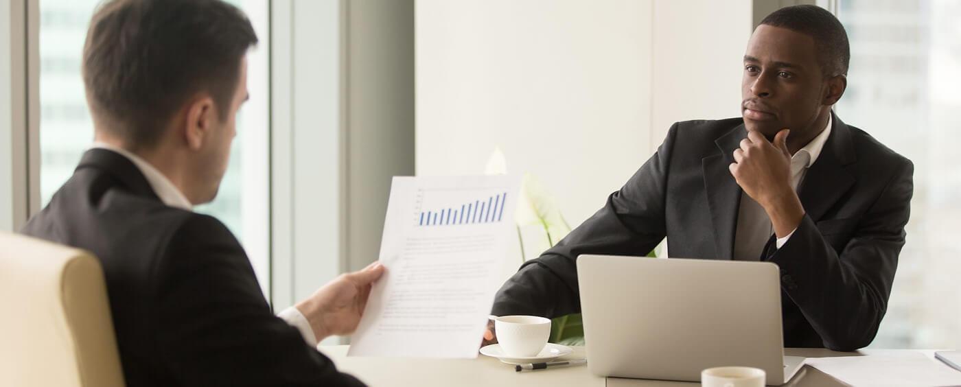 Manager se zaměstnancem probírá grafy výkonosti
