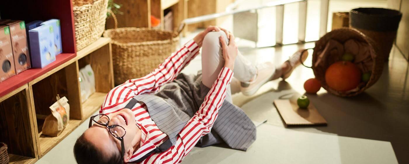 Prodavačka leží na zemi a drží si zraněné koleno