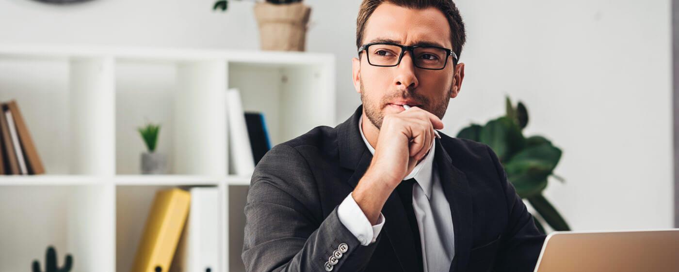 Muž u notebooku přemýšlející o následcích odstoupení od kupní smlouvy na nemovitost
