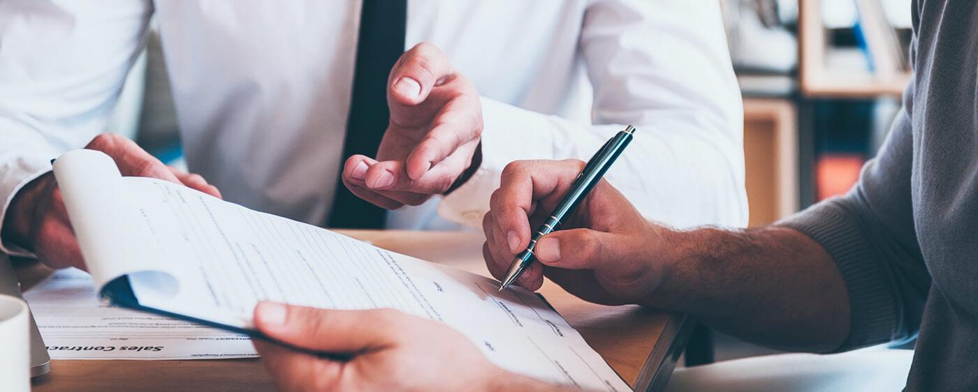 Dva muži podepisují odstoupení od kupní smlouvy nemovitosti