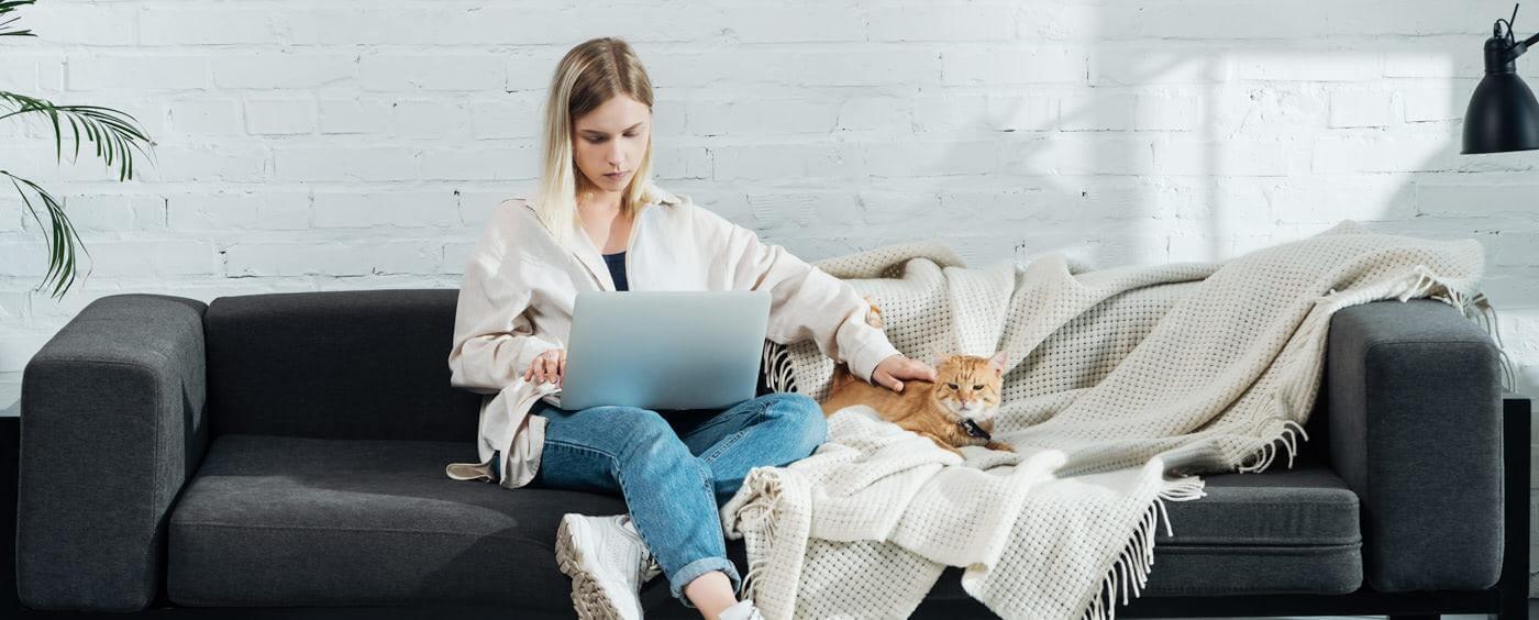 Žena sedí na svém gauči a pracuje na počítači