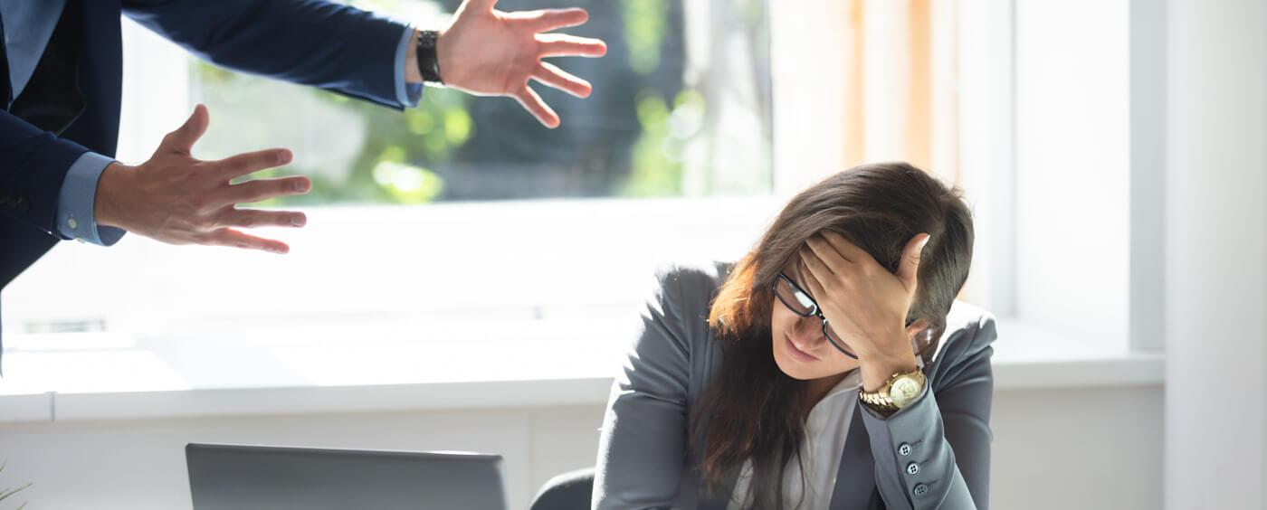 Žena za počítačem dostává kárání od svého šéfa