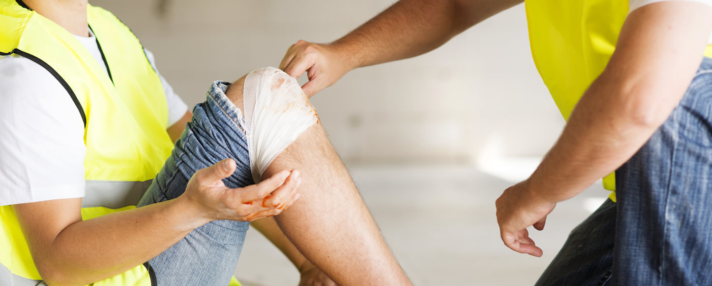 Kolega ošetřuje zraněnou nohu zaměstnance