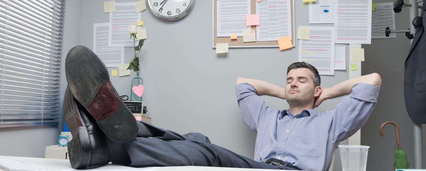 Muž relaxující v práci s nohama na stole
