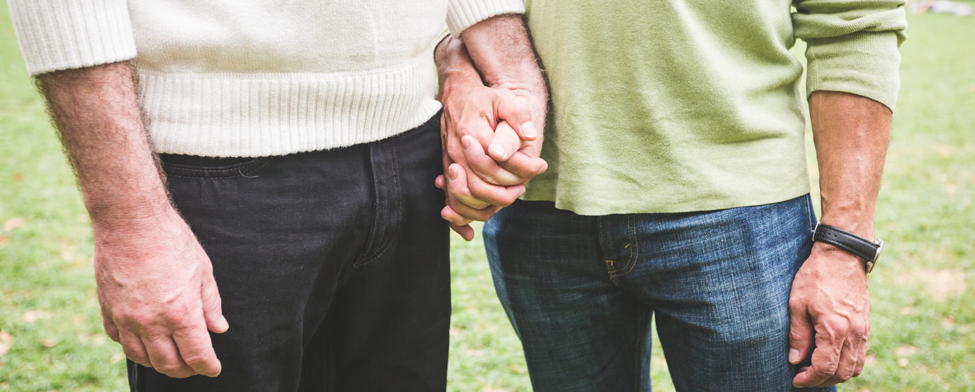 Detail na dva muže držící se za ruce