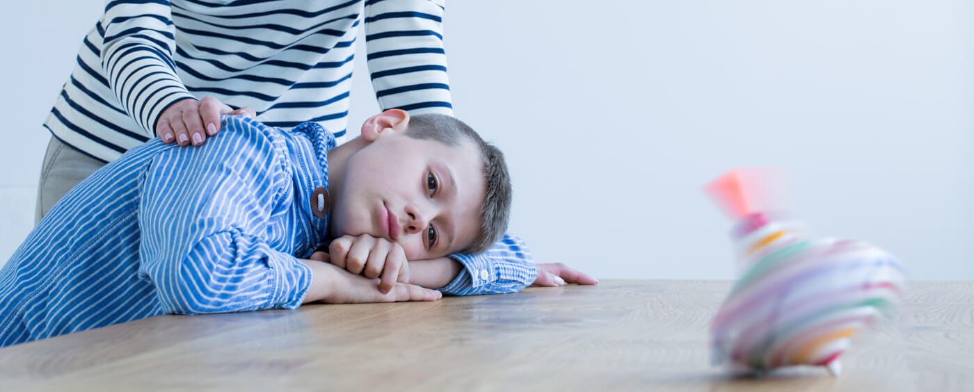 Smutný kluk je utěšován dospělou ženou