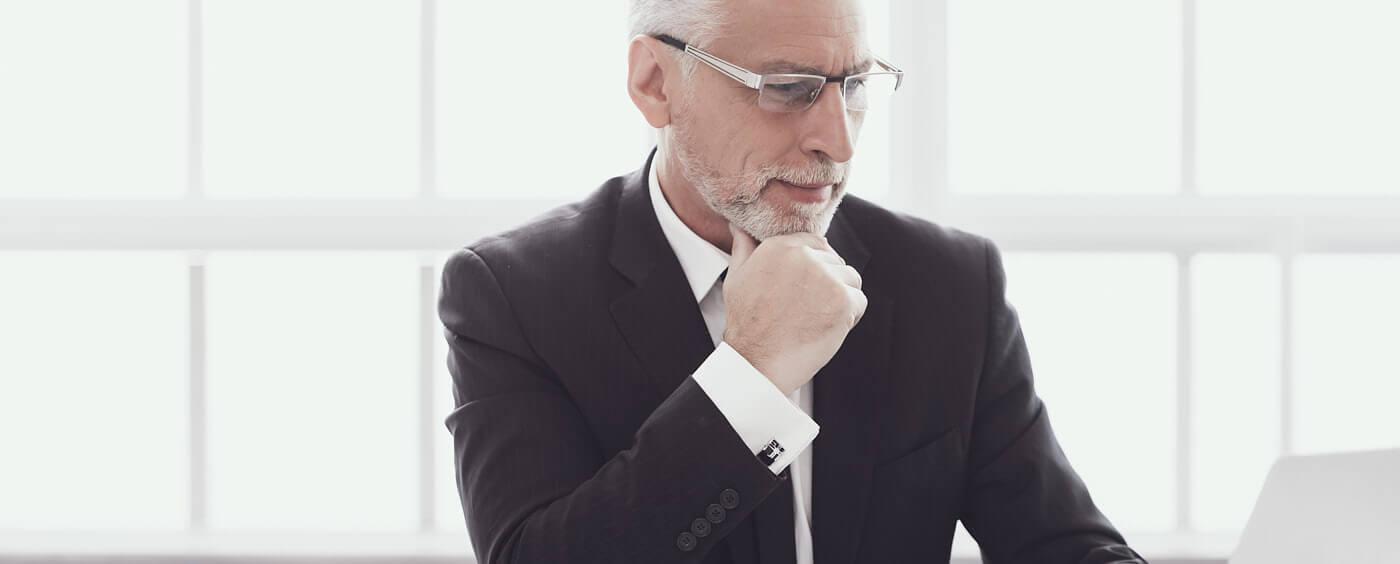 Zralý muž v obleku sedící za počítačem