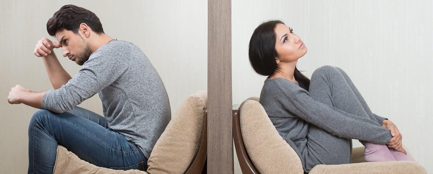 Muž a žena sedící k sobě zády