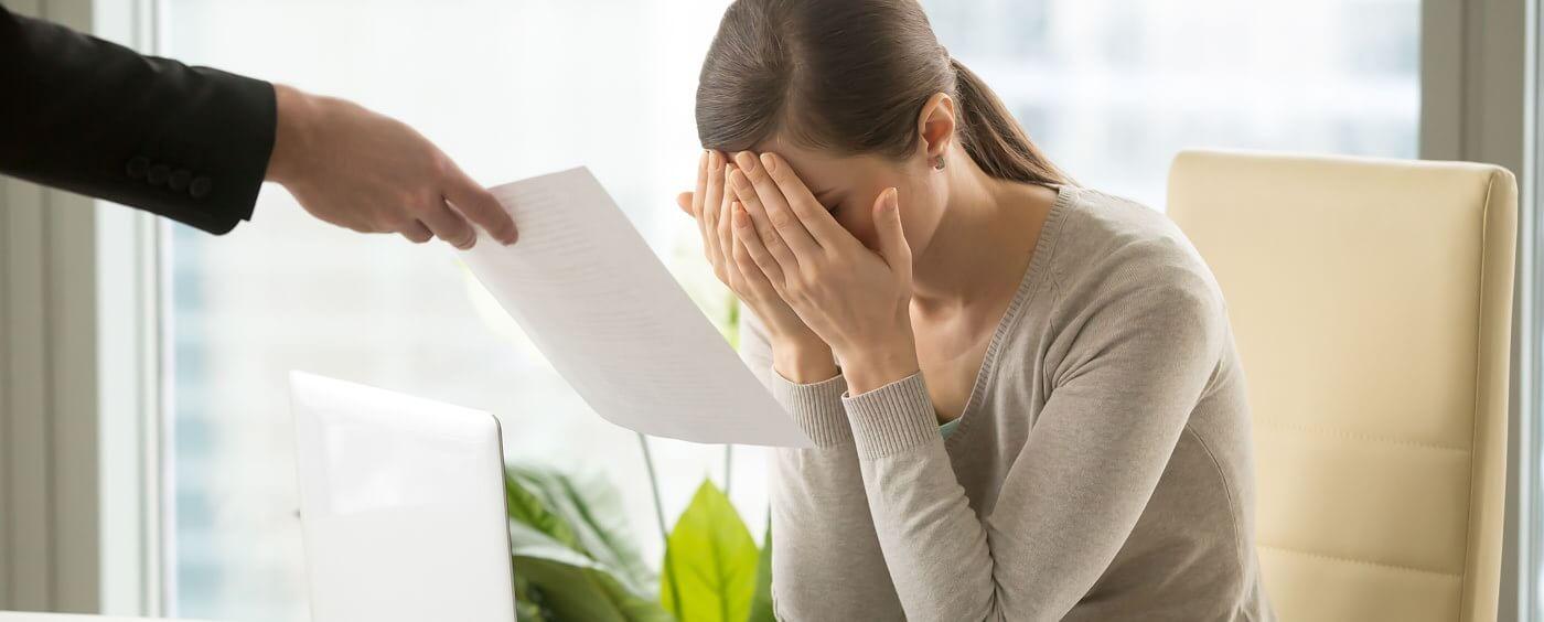Zdrcená žena sedící u počítače dostává výpověď