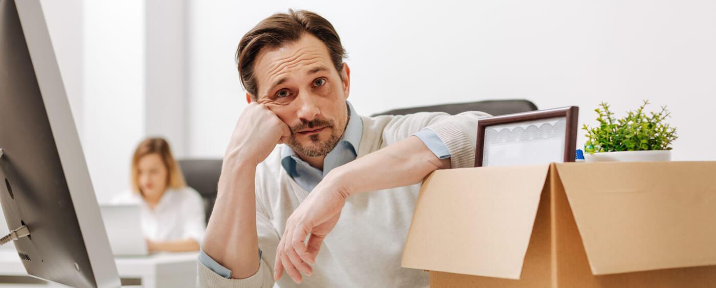 Zhrzený muž sedící u stolu a krabicí svých věcí