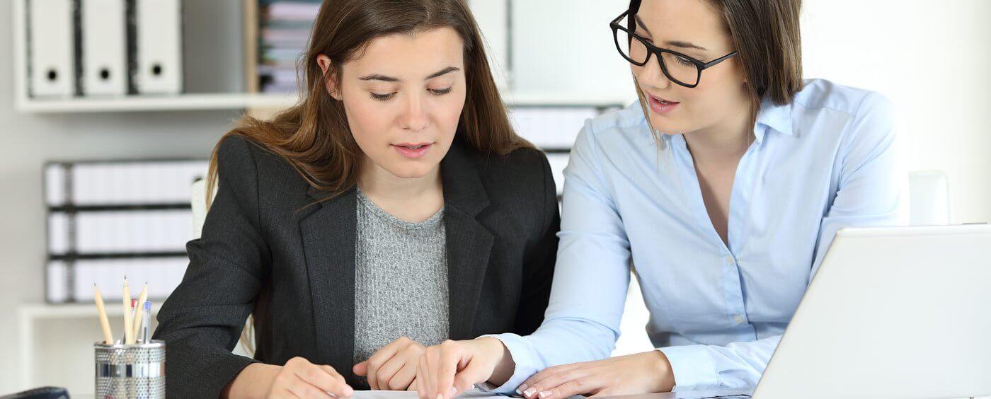Dvě ženy si povídají za pracovním stolem